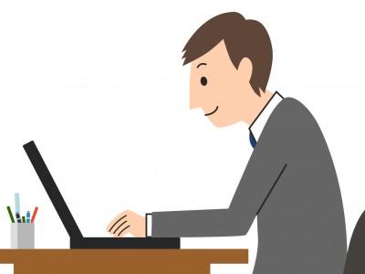 パソコンを使う猫背のビジネスマン