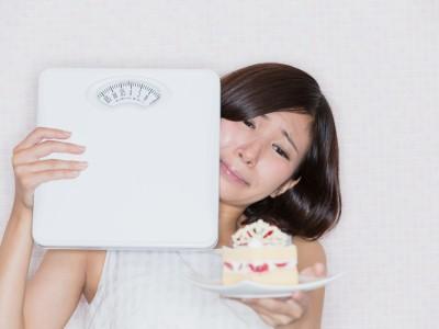 体重計 / ケーキを我慢する女性