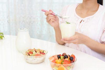 食前にヨーグルトを食べる女性