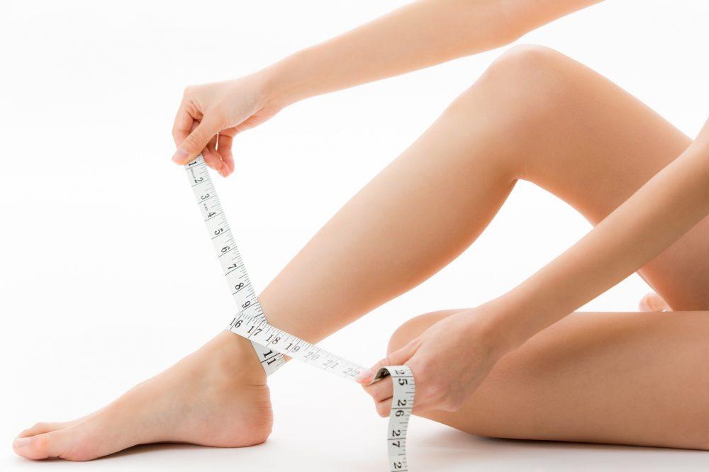 メジャーで足首を測る女性