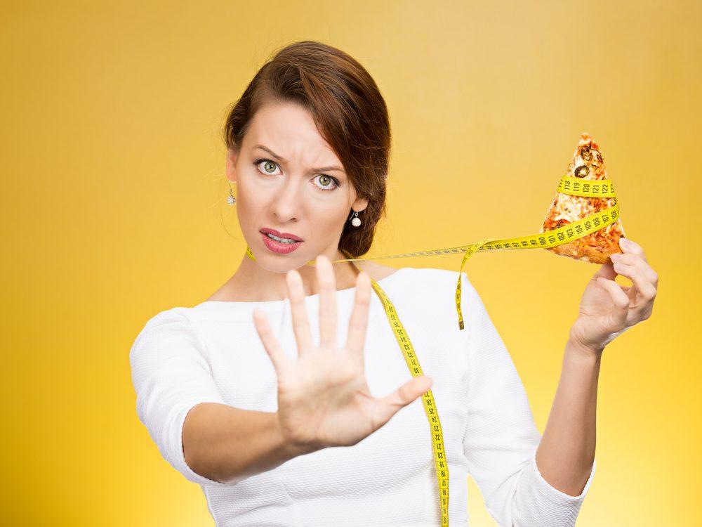 炭水化物(ピザ)を食べるのを止める女性