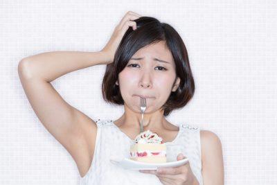 ケーキを食べるのを我慢する女性