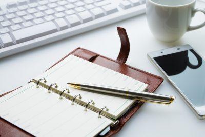 スマートフォン、パソコン、ノート、ペンが写った画像