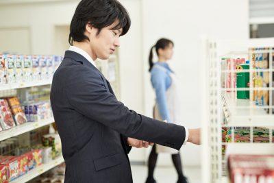 コンビニで商品を選ぶ男性