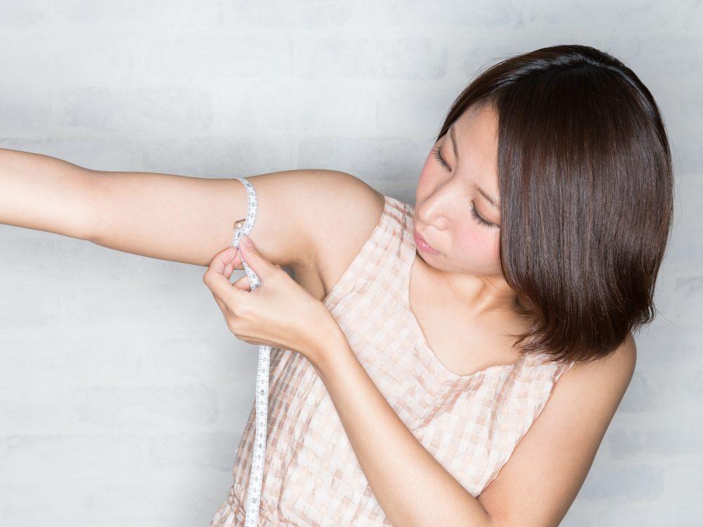 二の腕をメジャーで測る女性