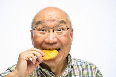 固い食べ物(煎餅を食べるシニア)