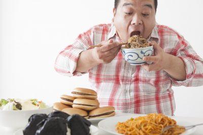 食事を摂る太っている中年男性