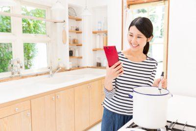 レシピを見ながらスープを作る女性