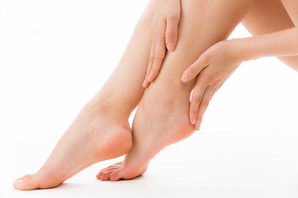 足首をマッサージする女性