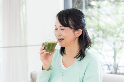 青汁を飲む中年女性