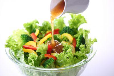野菜サラダにドレッシングをかける様子
