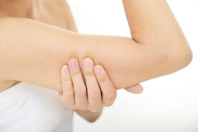 二の腕の脂肪を掴む女性