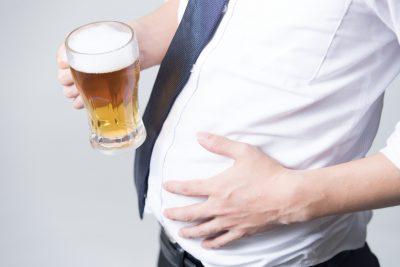 内臓脂肪が多いビールを持つサラリーマン