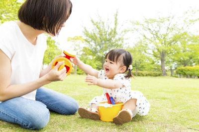 公園で赤ちゃんと遊ぶ親子
