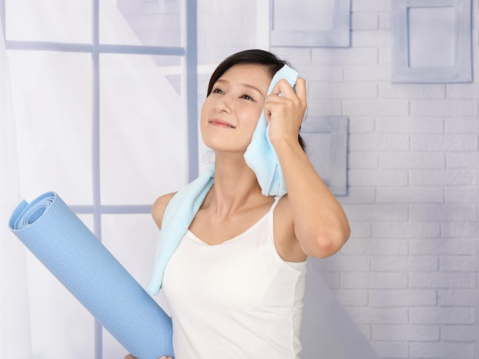 ヨガでかいた汗を拭く女性
