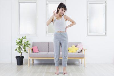 ダイエットに成功 体重計に乗る女性