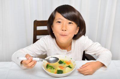 野菜たっぷりのシチューをたべる女の子