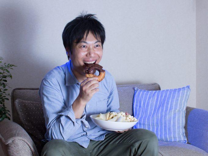 ドーナツを食べる夜遅くに食べる男性