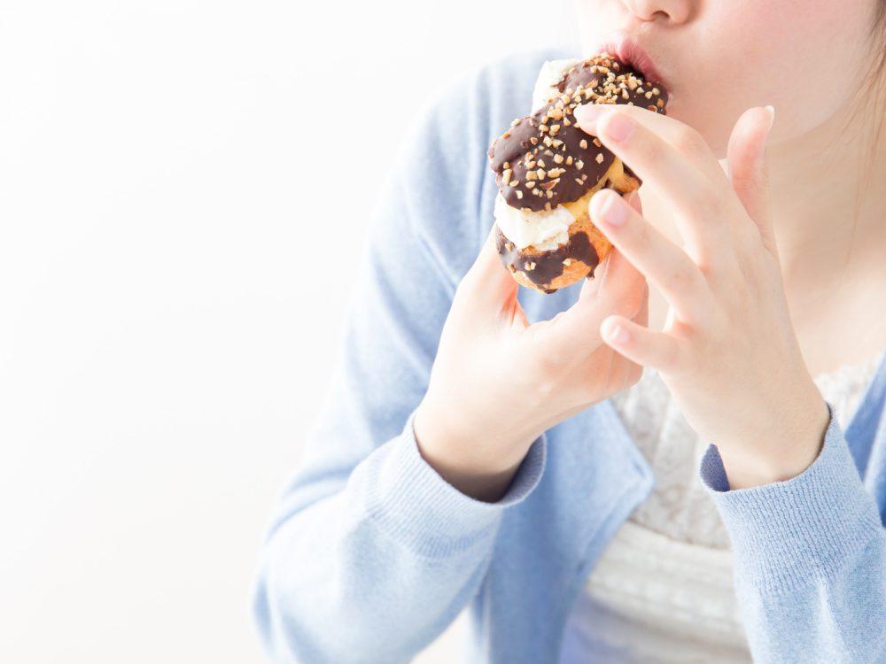 食べ過ぎてしまうドーナツを食べる女性