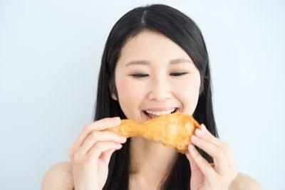 フライドチキンを食べる女性