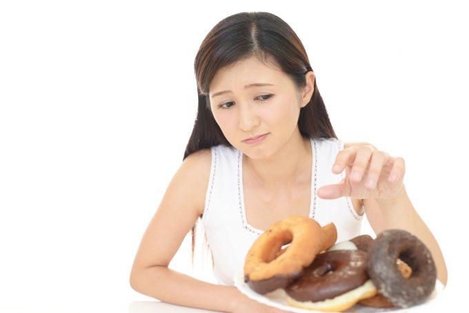 ドーナッツを食べるのを躊躇う女性