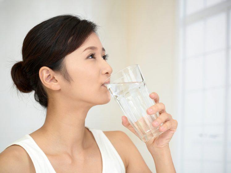 コップに入った水を飲む女性