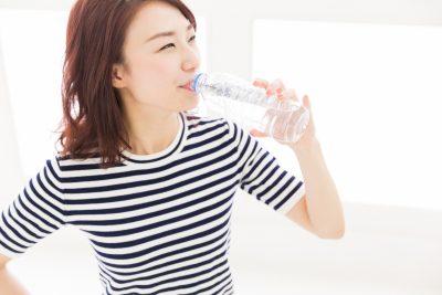 ペットボトルに入った水を飲む女性