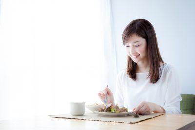 朝日を浴びて朝食を食べる痩せた女性