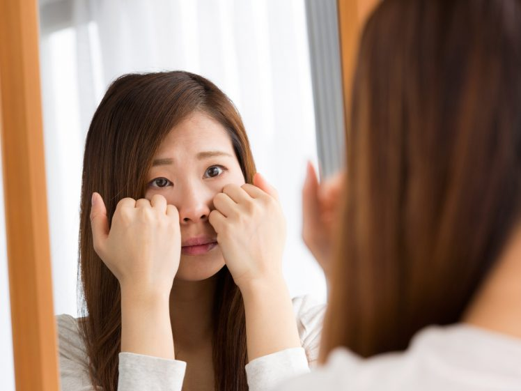 顔のむくみを気にする女性