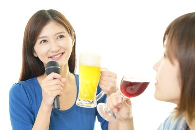 お酒を楽しみながら歌う女性