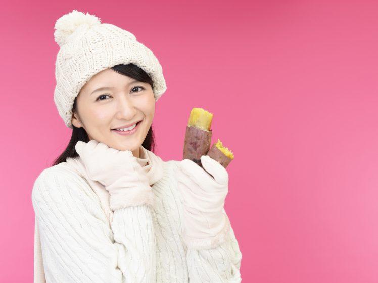 冬ダイエットのイメージ 焼き芋を食べる女性