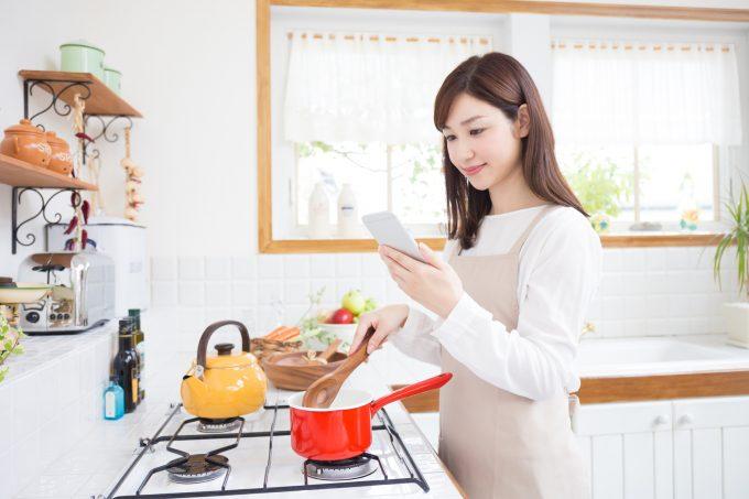 レシピを見ながら料理をする女性