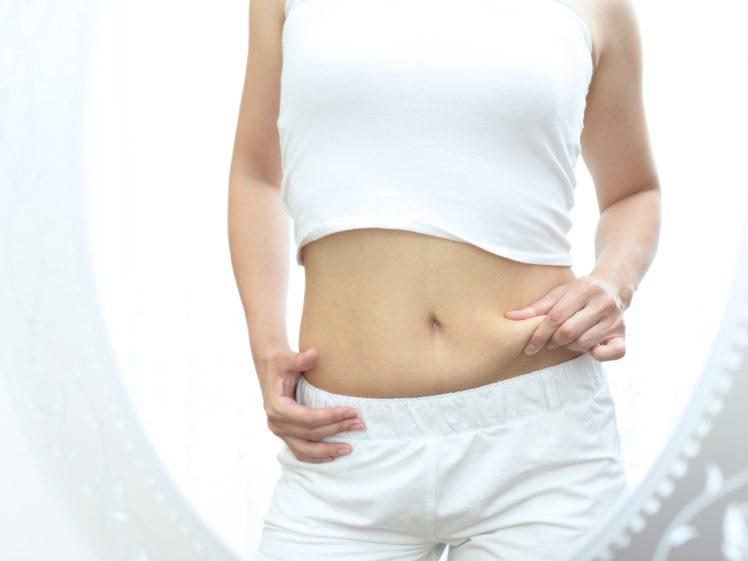 お腹の皮下脂肪を掴む女性