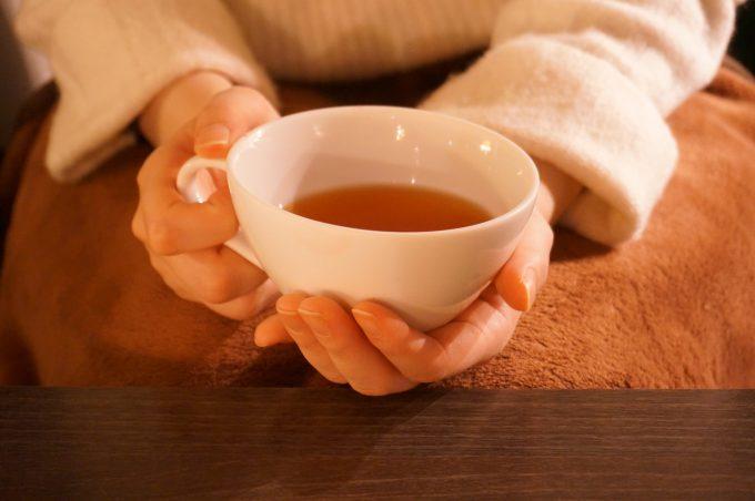 温かい紅茶を持つ女性の手