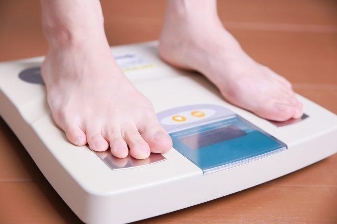 体重計に乗る女性 体脂肪計がついているモデル