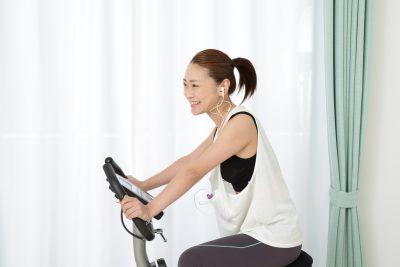 音楽を聴きながらエアロバイクを漕ぐ女性
