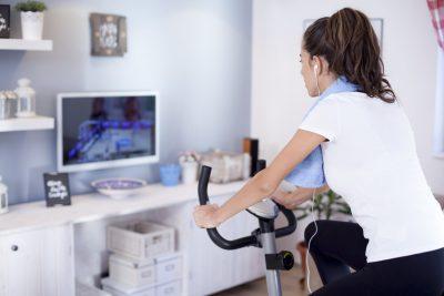 テレビを見ながらエアロバイクを漕ぐ女性