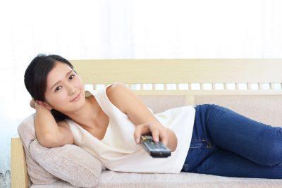 テレビ見ながらゴロゴロする女性