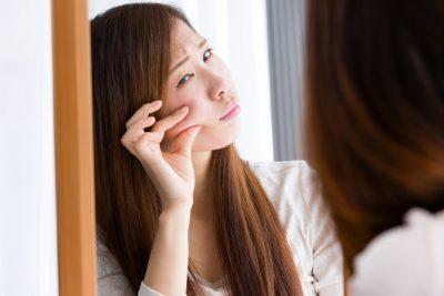 頬をつまむ女性