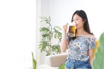 夕食時にビールを飲む女性