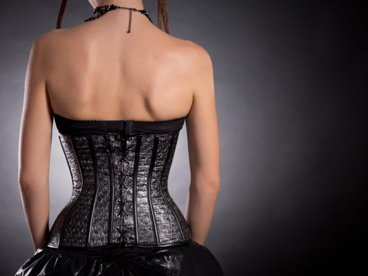 黒のコルセットを身につけた後姿の女性