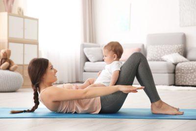 赤ちゃんをあやしながら腹筋する女性