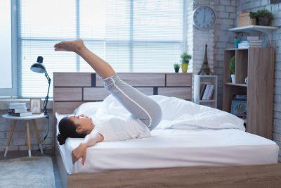 朝食前にベッドで軽い運動をする女性