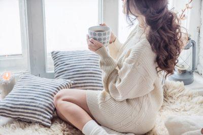 部屋でコーヒーを飲んで寛ぐ女性