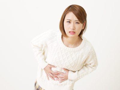 胃がもたれて苦しむ女性