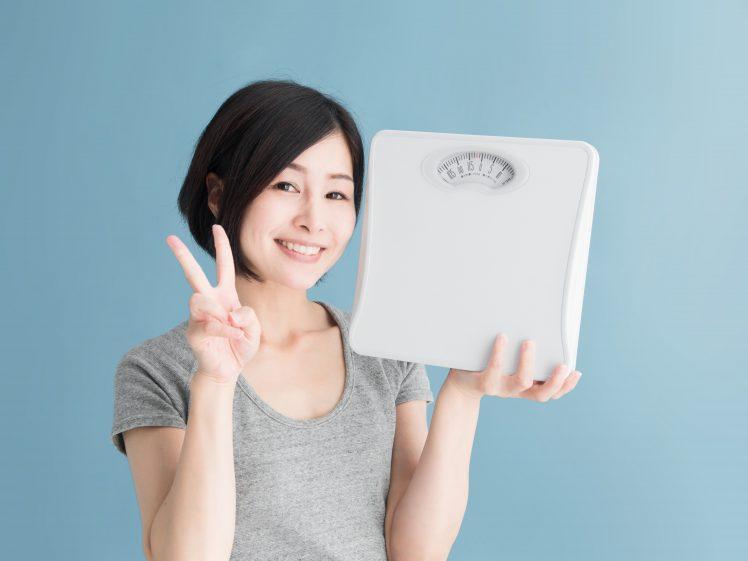 ダイエットに挑戦する体重計を持つ30代女性