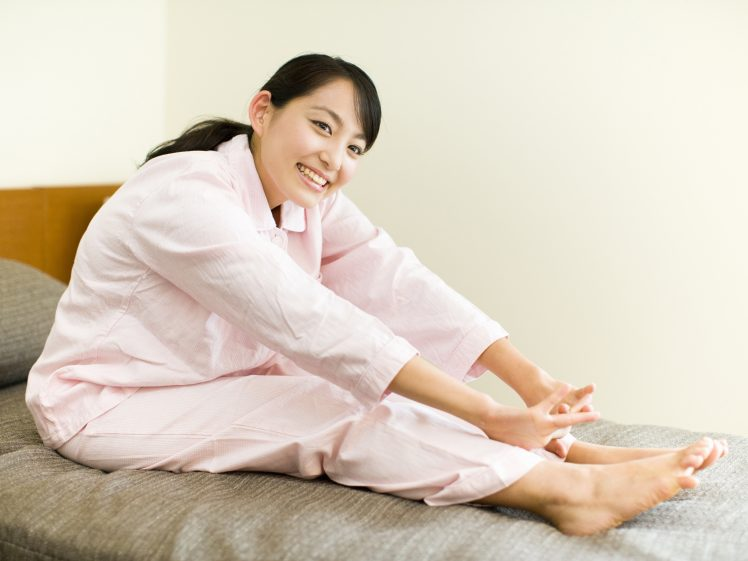 寝る前にパジャマでストレッチをする女性
